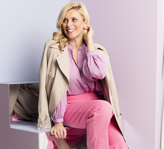 Brooke Falvey wearing a beige trench coat with a lilac, pink pants and silver heels