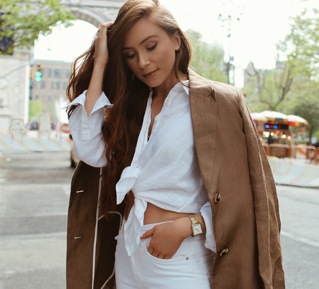 Erika Fox wears a white linen shirt, white jeans and brown coat