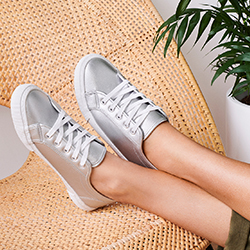 Woman wearing a pair of silver sneakers