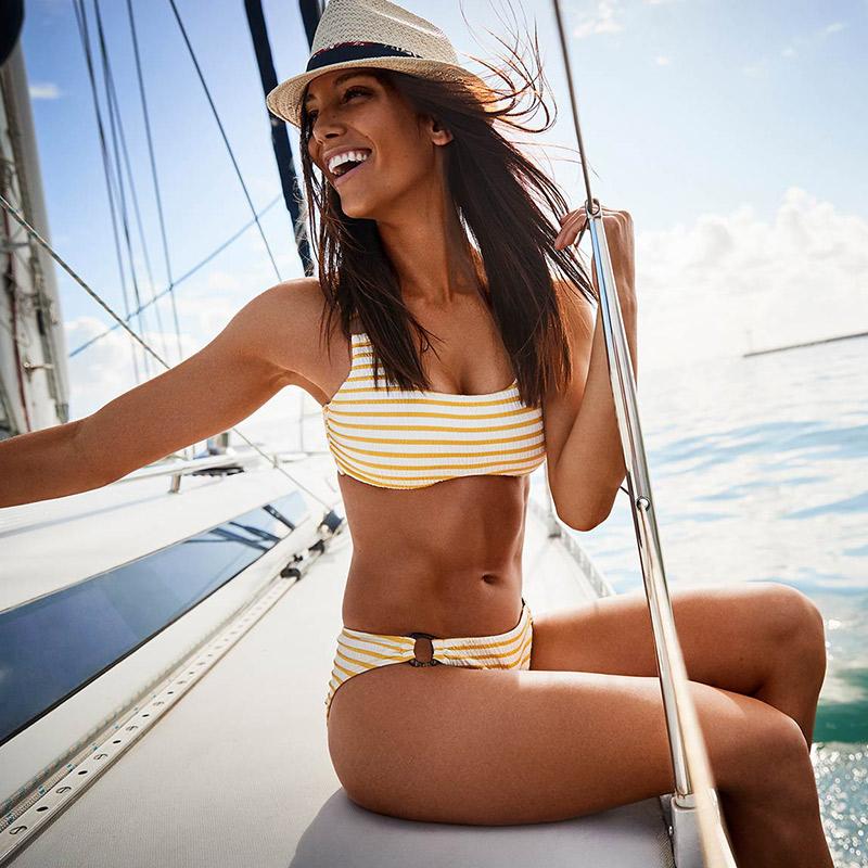 Model wears yellow striped bikini