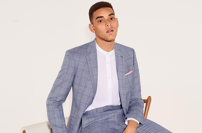 Man wearing pale blue checked suit with white grandad collar shirt